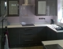 dark fitted kitchen with light worktops