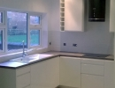 white fitted kitchen with dark worktops