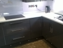 dark fitted kitchen and sick with light worktop